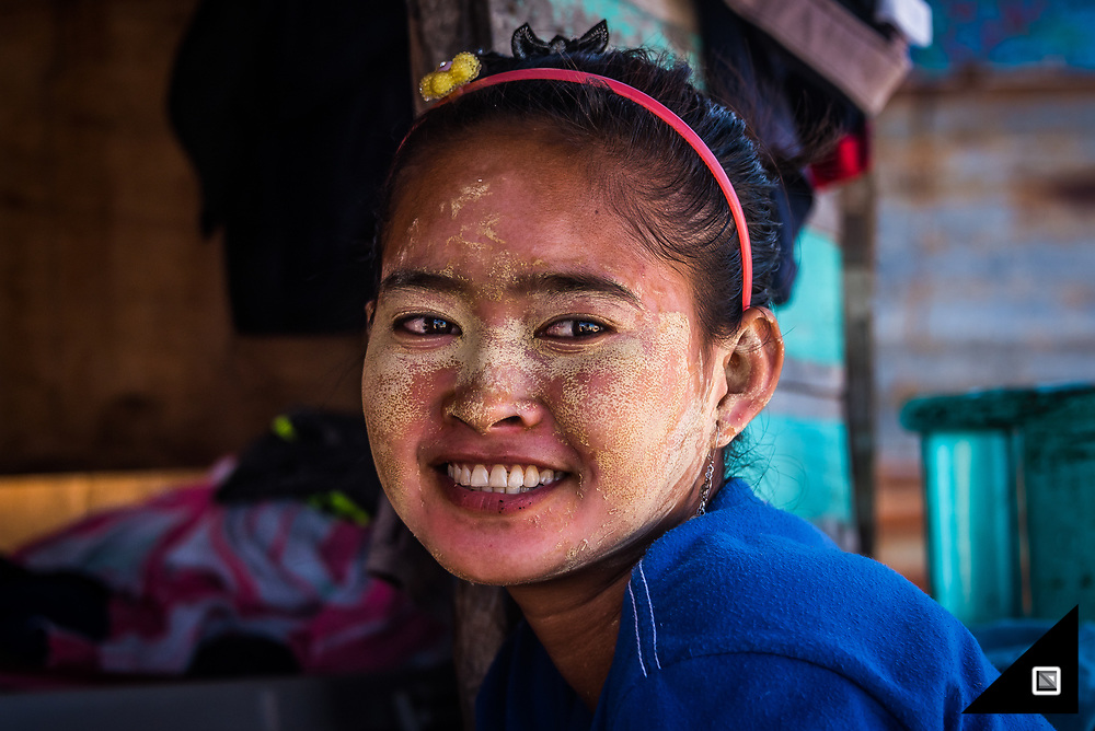A Bajau girl laughing about me coming to visit them in a one-man canoe. The ethnicity even produces an everyday sunscreen called Borak Buas mainly based on rice powder which the females use to protect their skin from the strong sun rays. Especially unmarried women use it a lot, with the effect that their face looks flawless and therefore attracts a potential spouse.