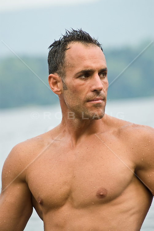 Wet shirtless man waist up looking over his shoulder