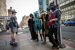 © Licensed to London News Pictures . 25/07/2015 . Manchester , UK . At a bus stop on Deansgate . Visitors to Comic Con on the streets of Manchester after venue - Manchester Central's - doors are shut . Photo credit : Joel Goodman/LNP