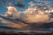 Rainstorm with lightning over the northern Rio Grande Valley at sunset, with mesas from the Pajarito Plateau in the foreground, New Mexico, © 2008 David A. Ponton