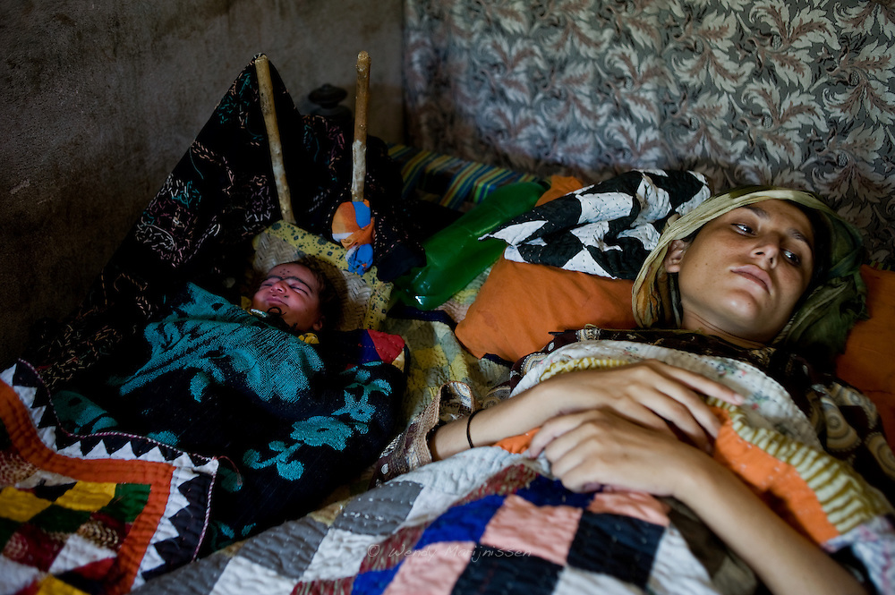22-year-old Rashida gave birth at home to her baby girl the previous day assisted by her auntie Mirzadi who works a dai. <br /> She suffered two previous miscarriages and lost her husband 18 days ago. <br /> She wanted a boy and is very disappointed the baby is a girl. Karachi, Pakistan, 2011