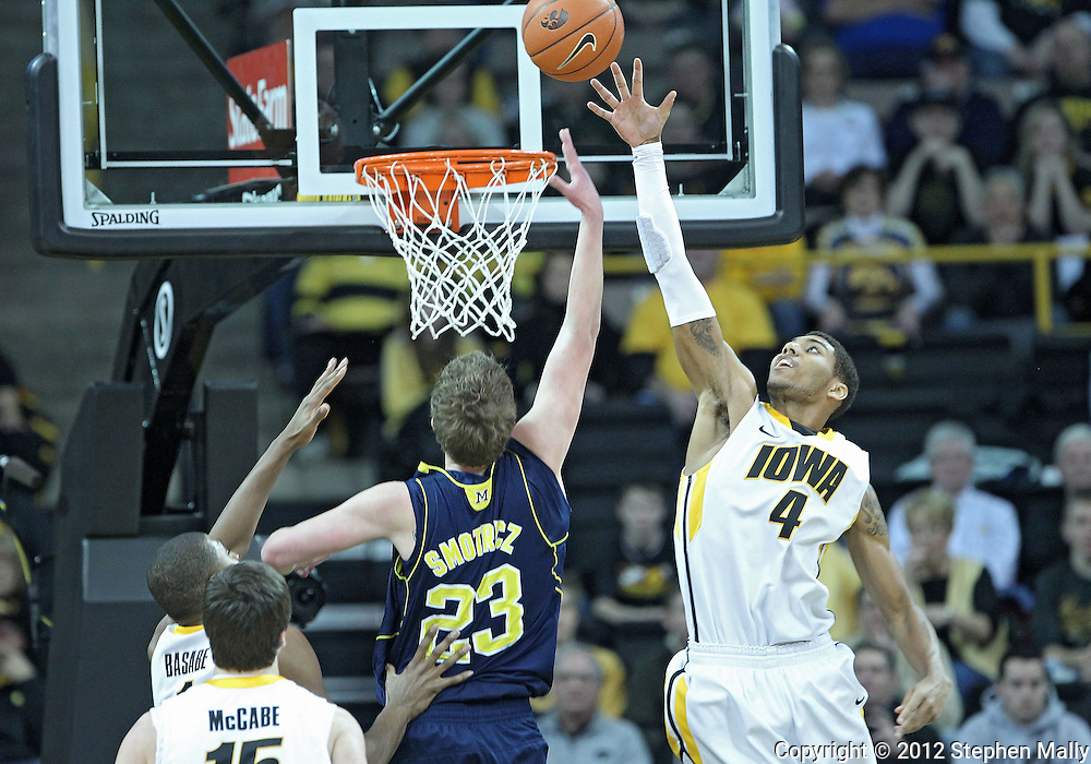 January 14, 2011: Iowa Hawkeyes guard/forward Roy Devyn Marble (4) tries to block a shot by Michigan Wolverines forward Evan Smotrycz (23) during the NCAA basketball game between the Michigan Wolverines and the Iowa Hawkeyes at Carver-Hawkeye Arena in Iowa City, Iowa on Saturday, January 14, 2011. Iowa defeated Michigan 75-59.