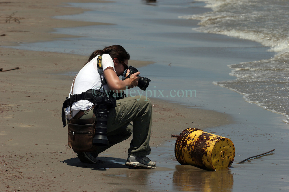 21 May 2010. Grand Isle, Lafourche Parish, Louisiana. .BP Macondo Well Disaster. Cheryl Gerber photographs an oily bucket washed ashore as authorities patrol the closed beaches advising tourists (and journalists) to leave as oil washes ashore in greater concentrations than previously seen on the once pristine beaches of Grand Isle. The economic and environmental impact is devastating with shrimp boats tied up, vacation rentals and charter boat fishing trips cancelled and police chasing tourists from the beaches just two hours drive from New Orleans..Oil from the Deepwater Horizon catastrophe is evading booms laid out to stop it thanks in part to the dispersants which means the oil travels at every depth of the Gulf and washes ashore wherever the current carries it. .Photo credit; Charlie Varley.