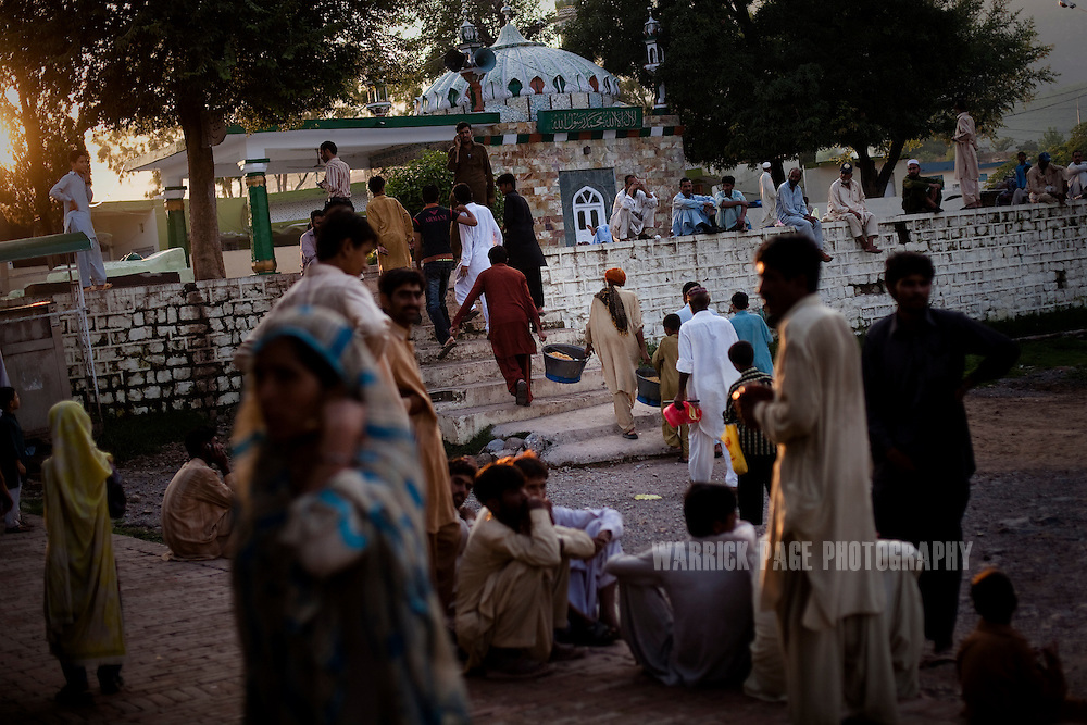 Impoverished families gather to receive a free meal of rice at Bari Imam Shrine, on August 8, 2011, in Islamabad, Pakistan. According to UN reports, hundreds of thousands of children in Pakistan suffer from severe-acute-malnutrition, with 15.1% of children experiencing acute malnutrition. Child malnutrition has breached emergency levels in Pakistan's Sindh province, after monsoon floods devastated the country's poorest region for a second year. Extreme poverty, poor diet and health, exposure to disease, and inadequate sanitation and hygiene annually produce alarming levels of malnutrition amongst children, but the floods have increasingly endangered an already vulnerable population. (Photo by Warrick Page)
