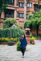 A young woman walks through the courtyard at Dwarika's Hotel in Kathmandu.