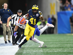 Michigan Wolverines running back Christian Turner (41) steps out of bounds as he is grabbed by Florida Gators defensive back Brady Walters (39) during the Chick-fil-A Bowl Game at  the Mercedes-Benz Stadium, Saturday, December 29, 2018, in Atlanta. ( AJ Reynolds via Abell Images for Chick-fil-A Kickoff)