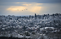 © Licensed to London News Pictures. 17/01/2016. Dorking, UK. Sun briefly breaks through the clouds at first light as snow covers the roofs of Dorking. Snow has fallen in the South East for the first time this winter. Photo credit: Peter Macdiarmid/LNP