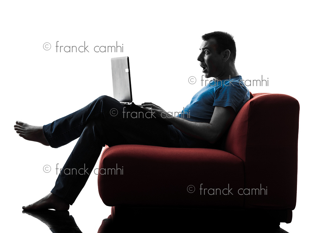 one caucasian man sofa couch computer computing laptop surprised in silhouette isolated on white background