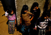 A group of Tz'utujil stand outside a home in a ally in Santiago Atitlan. Tu'utujil like many other Indians groups in Guatemala suffer from extreme poverty and are forced to make a living any way they can Feb. 2005. The Tz'utujil Indians and their village are best known for the occupation by the Guatemalan military in the 1980's civil war. The government set up a base in the city do to the fact that the city was used heavily by the ORPA guerrillas.   photo by darren hauck.....................................................