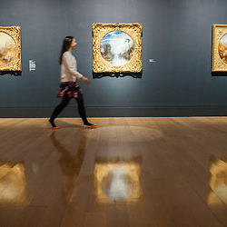 London, UK - 8 September 2014: a gallery assistant walks past 'Dawn of Christianity' by J.M.W. Turner.