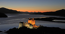 The historic floodlit Eilean Donan Castle with the sun setting behind the Cuillin mountain range on the Isle of Skye.. .. (c) Stephen Lawson | Edinburgh Elite media