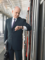 Mature Businessman checking time standing outside train in station