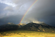 Is there gold in them there hills? A rainbow arcs toward Blanca Peak, surrounded by Ellingwood Peak and Little Bear Peak, in the Sangre de Cristo Range near Colorado's San Luis Valley.