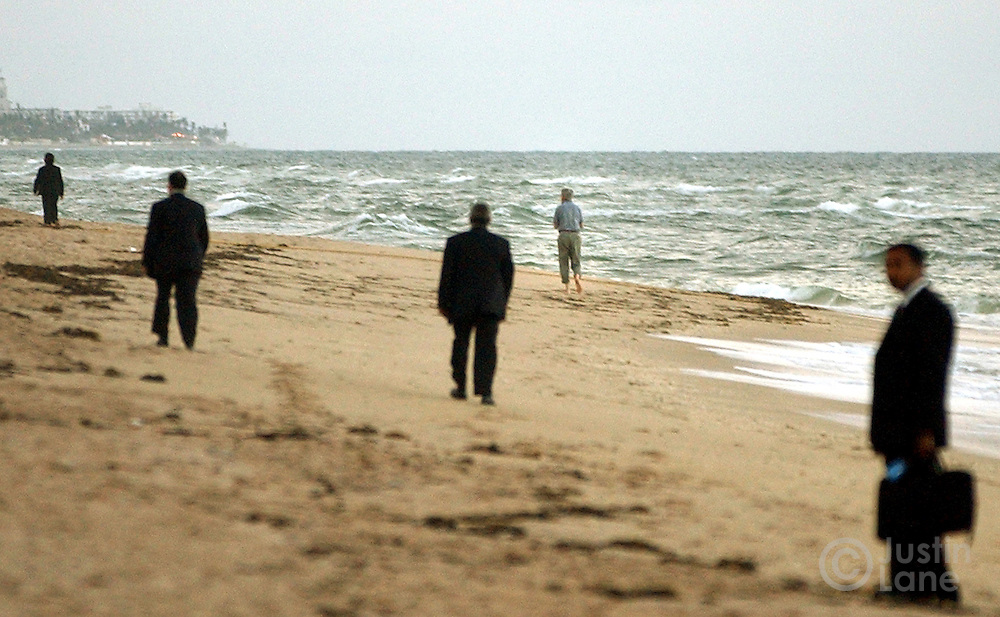 United States Senator and Democratic Candidate for President John Kerry, seen in background at right, takes a solitary walk along the beach, with 4 secret service agents in tow, outside of his hotel in West Palm Beach, FL Monday, 18 Oct, 2004. Kerry is campaigning in Florida today...EPA/JUSTIN LANE