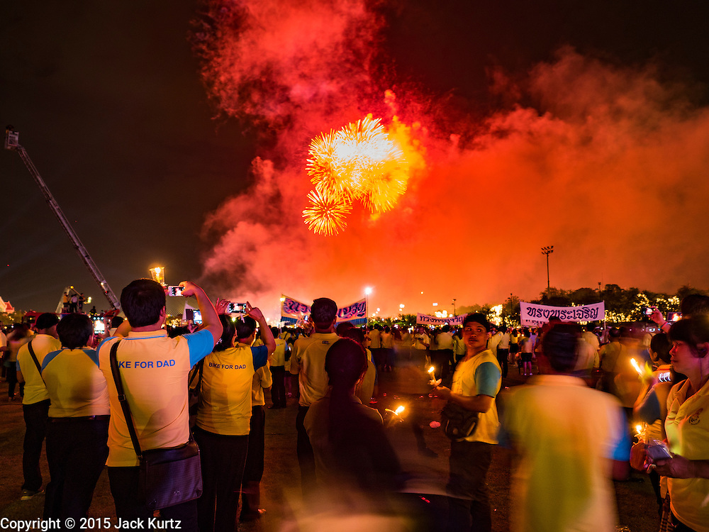05 DECEMBER 2015 - BANGKOK, THAILAND: Thais watch a fireworks display on the King's Birthday on Sanam Luang in Bangkok. Thais marked the 88th birthday of Bhumibol Adulyadej, the King of Thailand,  Saturday. The King was born on December 5, 1927, in Cambridge, Massachusetts. The family was in the United States because his father, Prince Mahidol, was studying Public Health at Harvard University. He has reigned since 1946 and is the world's currently the longest serving monarch in the world and the longest serving monarch in Thai history. Bhumibol, who is in poor health, is revered by the Thai people. His birthday is a national holiday and is also celebrated as Father's Day. He is currently hospitalized in Siriraj Hospital, recovering from a series of health setbacks.    PHOTO BY JACK KURTZ