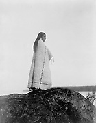 Cowichan woman, full-length portrait, wearing blanket, standing on rock, c1913.  Photograph by Edward Curtis (1868-1952).