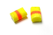 A pair of yellow earplugs used to reduce noise including noise caused by snoring