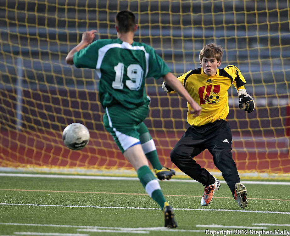 Washington's Gunnar Lenzen (00) comes up to try to block a shot by West's Bryton Ostler (19) during the game between Iowa City West and Cedar Rapids Washington at Kingston Stadium in Cedar Rapids on Monday evening, April 9, 2012. Washington won 3-2. (Stephen Mally/Freelance)