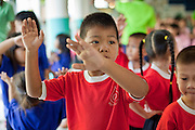 Sept. 23, 2009 -- BANGKOK, THAILAND: A boy learns Thai classical dance moves at the Duang Prateep Foundation school in the Khlong Toey slum area in Bangkok. The school is one of several private aid organizations working in the slum providing education and health care for residents. Khlong Toey slum in Bangkok, Thailand, is the largest slum area in Bangkok. Photo by Jack Kurtz