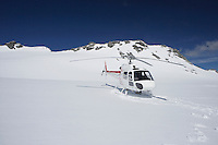 Helicopter landing on snowy mountain top