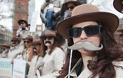 © Licensed to London News Pictures. 09/03/2012. London, England. Amnesty International campaigners wearing trench-coats with moustaches tried to remind Londoners at Soho Square today, 9 March, to watch Amnesty International's  Secret Policeman's Ball on Channel 4 at 10pm with an all-star cast of music and comedy talent in a special show featuring - among many others - Coldplay, Russell Brand, Jimmy Carr, Noel Fielding, Micky Flanagan, Sarah Silverman, Jon Stewart and Jack Whitehall to celebrate 50 years of the human rights organisation.  Photo credit: Bettina Strenske/LNP