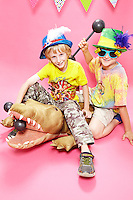 Two 9 year old boys sitting on a plush aligator wearing silly hats.<br /> Shot at Photoville Photo Booth, September 20, 2015