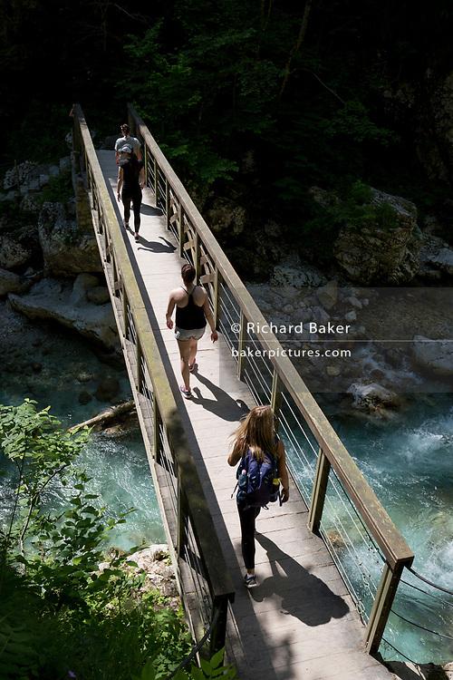 Visitors cross a bridge over the river Tolminka river at Tolminska Korita, on 20th June 2018, in Tolmin Gorge, Slovenia.