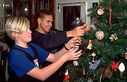 Friends age 14 hanging Christmas tree ornaments. St Paul Minnesota USA