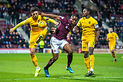 Uche Ikpeazu (#19) of Heart of Midlothian FC cuts between Ricki Lamie (#5) of Livingston FC and Marvin Bartley (#6) of Livingston FC during the Ladbrokes Scottish Premiership match between Heart of Midlothian FC and Livingston FC at Tynecastle Park, Edinburgh, Scotland on 4 December 2019.