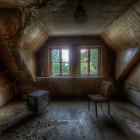 In the formar DDR East Germany an abandoned room interior with tv and chair by window