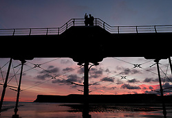 © Licensed to London News Pictures. <br /> 25/12/2016. <br /> Saltburn-by-the-Sea, UK.  <br /> <br /> A couple pose for a selfie on the pier as the first light of dawn illuminates the sky on Christmas morning in Saltburn by the Sea.<br /> <br /> <br /> Photo credit: Ian Forsyth/LNP