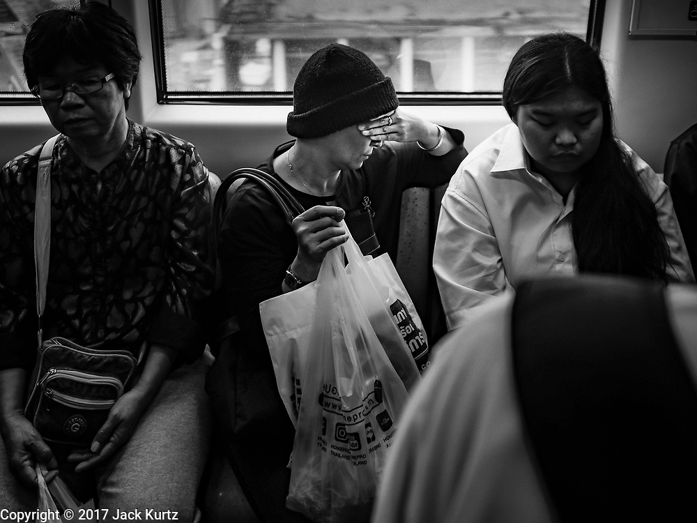 19 OCTOBER 2017 - BANGKOK, THAILAND: A woman on the BTS (Skytrain) Sukhumvit line rests neat the Thong Lo stop.     PHOTO BY JACK KURTZ