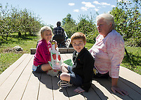 Katherine, Jesse and Elaine Baker take a tractor ride from Nicholas Rolfe to go apple picking at Smith Orchard in Belmont on Sunday afternoon.  (Karen Bobotas/for the Laconia Daily Sun)