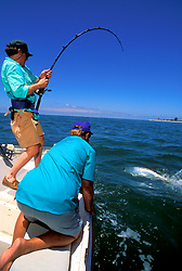 Stock photo of two men sport fishing for tarpon off of the Florida coast