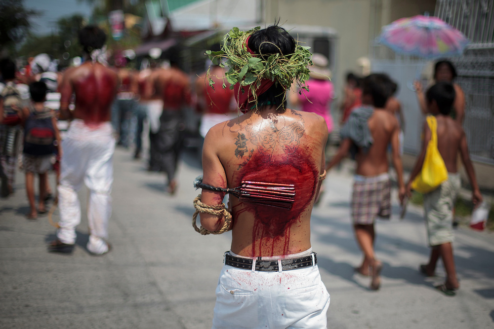 Hooded penitents lay prone on the pavement during flagellation ritual to atone for their sins in observance of Holy Week Thursday, April 5, 2012 at Los Angeles city, Philippines. Such practice is rejected by the Catholic church.