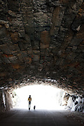 The figures of a woman and her dog on a leash are silhouetted against the light from the end of a tunnel in Central Park in Manhattan, New York City as they are walking along a path.