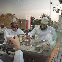 Men enjoy chatting at a cafe and tea house adjacent to a mosque before the call to prayer, in Muscat.