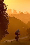 UNITED KINGDOM, London: 04 August 2015 A cyclist takes a ride through Richmond Park this morning in front of the London landscape and a rising sun . Rick Findler / Story Picture Agency