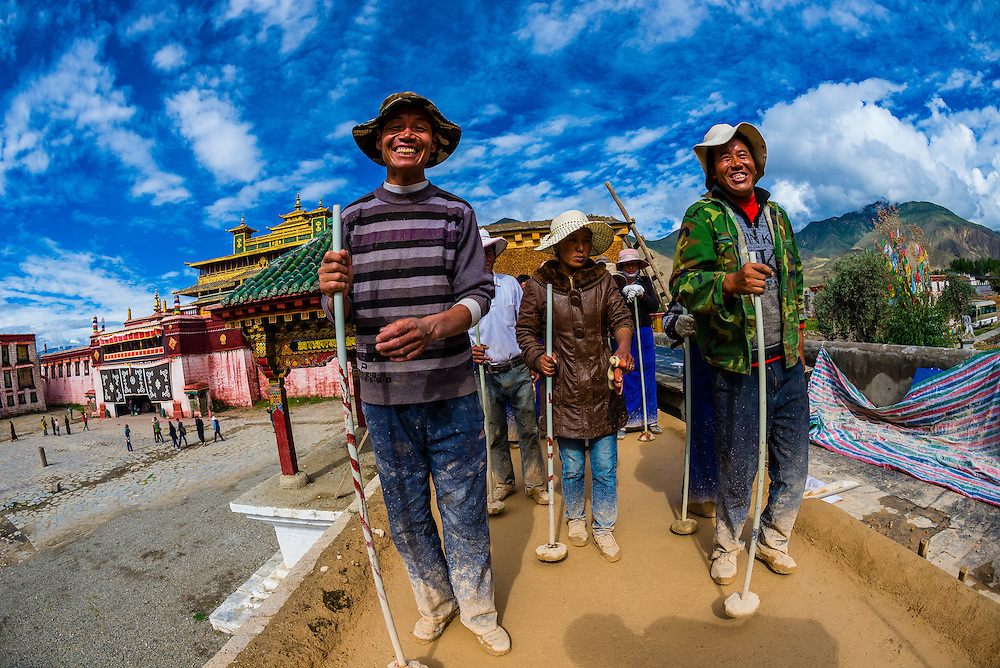 Workers tamp down wet cement atop a building at Samye Monastery, Chatang, Lhoka (Shannan) Prefecture, Tibet (Xizang), China