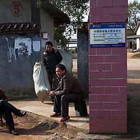 Hunan, Liuyang, Dec. 19..2013 : guards LUO Jian (L)   and XIAO Hui ( R )   sit at the entrance  of a firecrackers factory  while worker Zhou Zhonghua passes trough with a bag of rockets.