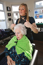 Hairdresser styling old lady's hair.