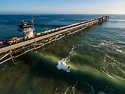 Aerial photo of a surfer going left at the San Clemente pier in Southern California.