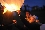 CORRECTS HOLINGER: Bruce Holinger (right) of Warrington, Pennsylvania lights a lantern as Tommy Cornell, 12 looks on before they released it into the air during the Lanterns of Hope event Saturday October 24, 2015 in Buckingham, Pennsylvania. The event was a benefit for Make A Difference Children's Foundation to help children in shelters in the United States and school children in Nigeria. (Photo by William Thomas Cain)