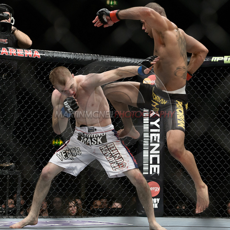 """LONDON, ENGLAND, FEBRUARY 16, 2013: Michael McDonald (L) covers up from a flying knee by Renan Barao during """"UFC on Fuel TV 7: Barao vs. McDonald"""" inside Wembley Arena in Wembley, London on Saturday, February 16, 2013 (© Martin McNeil)"""