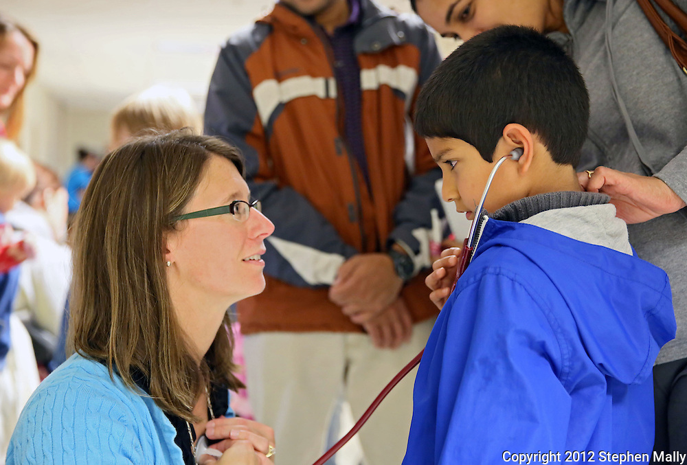 Prem Kulkarni (from right), 7, of Cedar Rapids, listens to the heart beat of Coe College nursing instructor Sara Scott during the 10th annual Playground of Science at Peterson Hall on the Coe College campus in Cedar Rapids on Thursday, October 25, 2012.