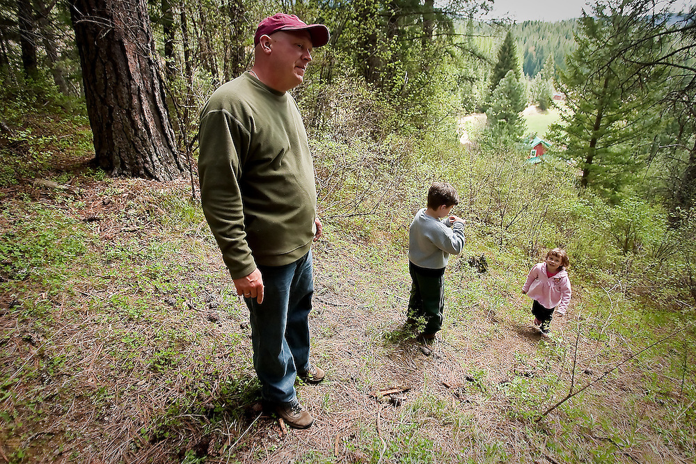 "JEROME A. POLLOS/Press..Kevin Croffoot stands on a hillside Friday with his children, Austin, 7, and Danica, 4, where it is believed his two-year-old nephew began his near two-mile trek through the woods Tuesday prompting a massive search. ""We didn't even think of that area as an option because of how rugged the terrain is,"" Croffoot said about the wooded hillside behind his farm."
