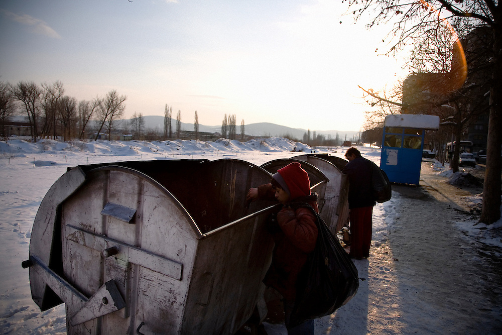 Roma search through garbage bins on the North bank of the Ibar River in Mitrovica.