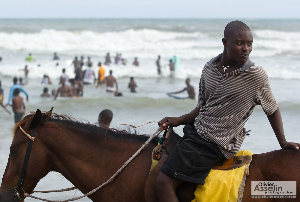 A man sits on a horse at Labadi Beach in Accra, Ghana on Sunday October 8, 2007. Also known as La Pleasure Beach, it is one of the city's most popular hangouts, especially on Sunday afternoons. For a small fee, visitors can ride horse along the ocean.