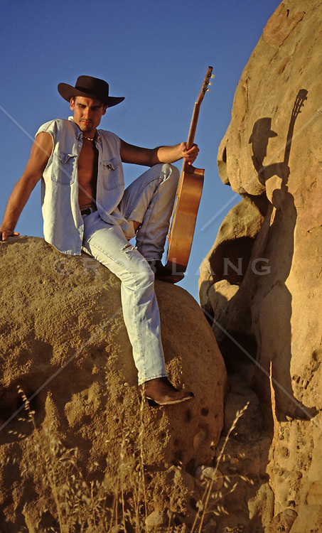 cowboy holding a guitar while sitting on rocks