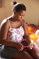 A weaver of Zamampilo trims a sisal braid